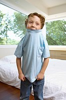 Boy pulling T_shirt over his head