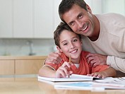 Man with boy sitting at table with homework smiling