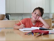 Boy sitting with homework smiling