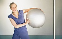 Woman holding a pilates ball laughing