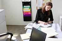 Businesswoman working on paperwork in office