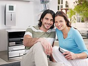 Couple sitting on rug holding television remote