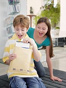 Young boy opening package while girl watches