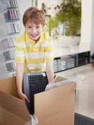 Boy opening box with computer inside