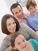 Couple with young boy and girl sitting on sofa together smiling