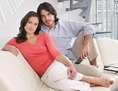 Couple relaxing on sofa with television remote