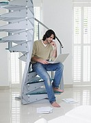 Man sitting on stairs with laptop and paperwork