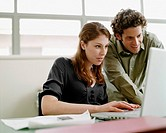 Two businesspeople in office looking at laptop
