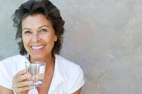 Woman smiling holding a glass of water outdoors