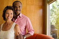 Couple standing in modern home smiling