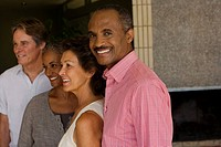 Two couples standing in modern home smiling with one man looking to camera