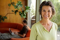 Woman standing smiling with man in background on laptop