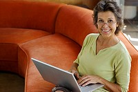 Woman sitting on sofa with laptop in modern home