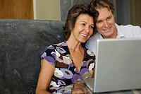 Couple looking at laptop at kitchen table