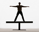 Man standing on a plank with arms out