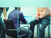 Three businesspeople in an office at a laptop (thumbnail)
