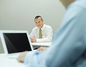 Businessman sitting in office with coworker in foreground