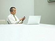 Businessman in office on mobile phone with laptop on table