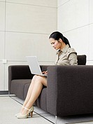 Businesswoman sitting on sofa with laptop