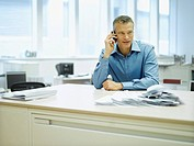 Businessman in office on his mobile phone