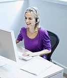 Businesswoman wearing a headset at her desk smiling