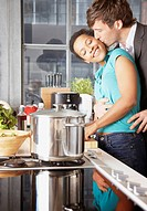 Couple kissing and embracing in kitchen
