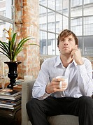 Man sitting on couch with coffee in modern home