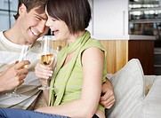 Couple with champagne sitting on sofa in living room