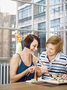 Couple eating sushi in modern home