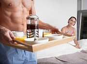 Man bringing a woman breakfast in bed