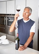 Man looking at glass of wine in kitchen