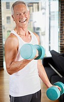 Man lifting dumbbells in living room