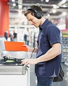 Man wearing headphones at record player in store (thumbnail)