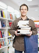 Man in store with stack of books