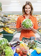 Woman holding watermelon while grocery shopping