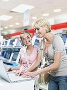 Woman and girl on laptop in store