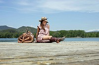 Woman sitting on dock with large bag