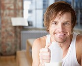 Man with milk jug in modern home