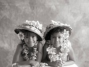 Hawaii, Two local sisters wearing palm frond hats and plumeria leis Sepia photograph