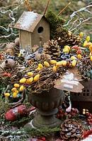 A bird house in a winter arrangement