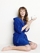Woman in blue bathrobe using body cream