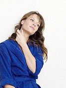 Woman in blue bathrobe with small bottle