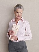 Senior adult in business clothing holding newspaper