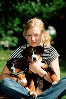 girl with two Bernese mountain dog puppys