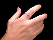 Personal radiation monitor on a person´s finger  This is an extremity TLD thermoluminescent dosimeter  It is worn by people who are exposed to radiati...