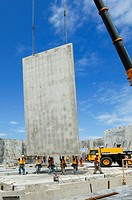 Tilt-up concrete construction  Construction workers holding a concrete wall as a crane lifts it into place on the foundations of a new building  They ...