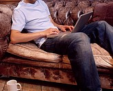 Young man sitting on sofa, using laptop, low section