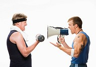 Fitness trainer yelling through megaphone at mature man exercising with dumbbells, side view