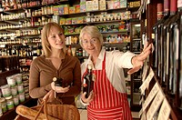 Shop assistant in delicatessen helping female customer select wine