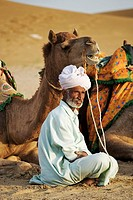 India, Jaisalmer, man sitting by camel in Great Thar desert